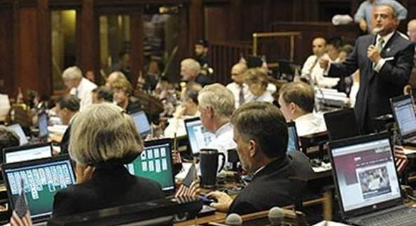 Just One More Thing PICTURE WORTH A TRILLION DOLLARS House Minority Leader pictured standing, far right, speaks while colleagues play solitaire Monday night as the House convened to vote on a new