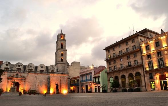 Plaza de San Francisco de Asis, a paved space with fluttering pigeons, framed by historic buildings such as the Convent and the Church of St.
